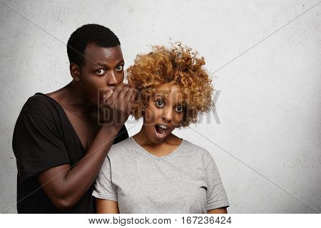 Attractive Young African Man Sharing Secret Or Whispering Gossips Into His Fashionable Girlfriend's