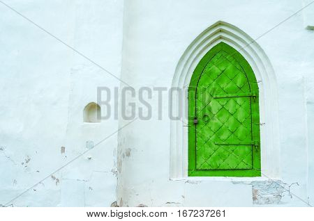 Architecture background - old metal door on the white stone wall, architecture background with architecture details