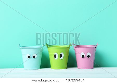 Colorful Buckets With Googly Eyes On A Green Background