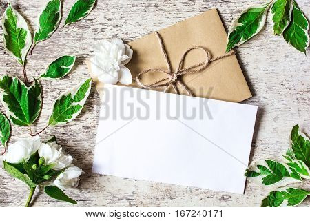 blank white greeting card with white jasmine flowers and envelope with leaves on white wooden background. top view. mock up