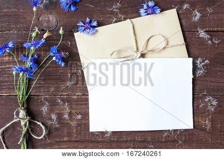 blank white greeting card with wild blue cornflowers bouquet and dandelion seeds with envelope mock up on dark wooden background. top view.