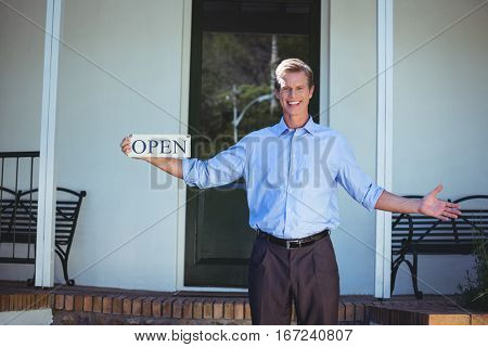Handsome businessman holding an open sign in front of a house