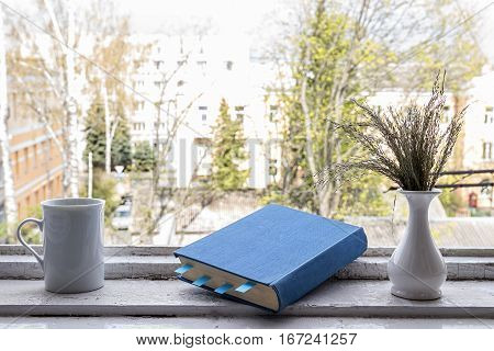 Blue Book with bookmarks and a cup of coffee on the window. Reading and learning.