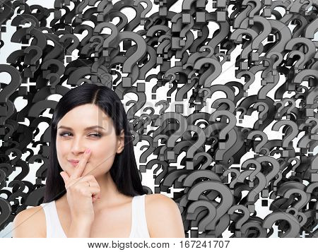 Portrait of a cunning woman in a tank top against black question marks background. Concept of multiple questions that need to be answered.