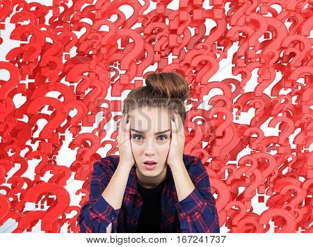 Portrait of a stressed out teen girl sitting against red question marks background. Concept of multiple questions that need to be answered.