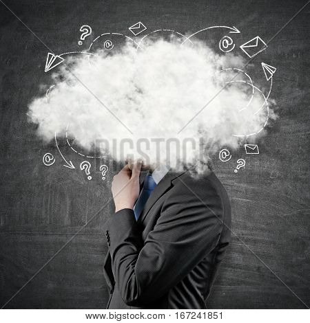 Side view of young businessman with head in the clouds. Concept of contemplation