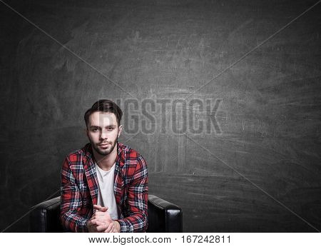 Handsome european guy sitting on chalkboard background with copy space