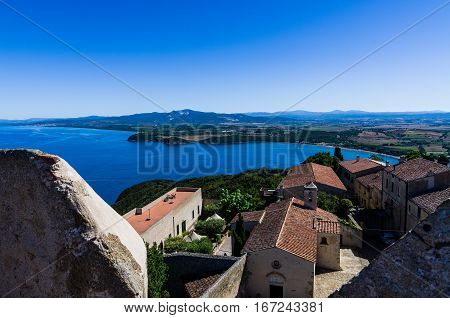 Baratti Gulf taken from Populonia Castle and its ancient houses in a sunny summer day