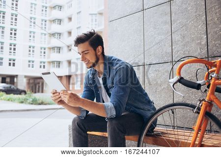 Young man using the tablet sitting on the bench. Smiling attractive guy watching funny video or reading an interesting article whike h has a break. Urban background