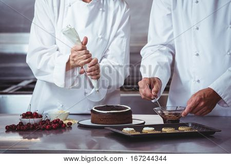 Chefs decorating a cake in a restaurant