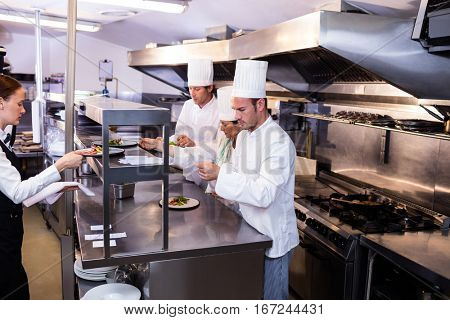 Group of chef preparing food for client in commercial kitchen
