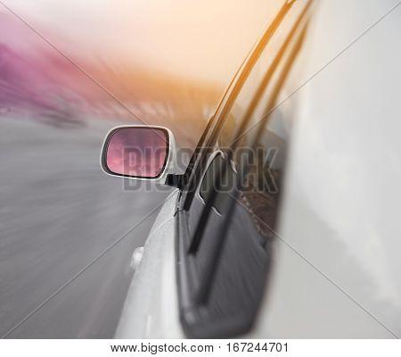 white car driving on freeway at sunset