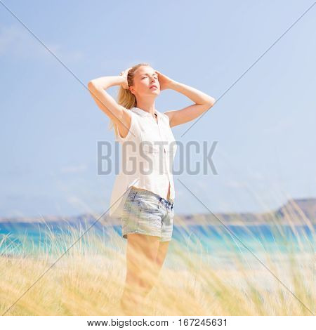 Relaxed woman enjoying sun, freedom and life an a beautiful beach. Young lady feeling free, relaxed and happy. Concept of vacations, freedom, happiness, enjoyment and well being.