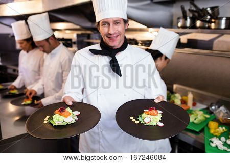 Happy head chef presenting his food plates in the commercial kitchen while team working behind him