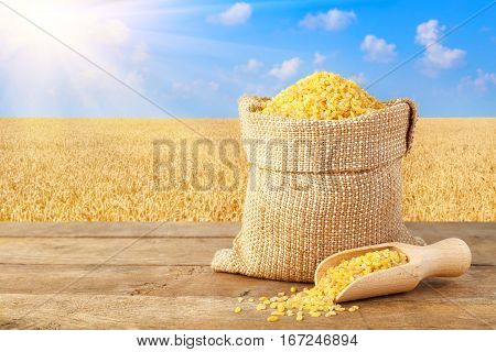 Bulgur or couscous in sack. Bulgur in bag on table with field of wheat on the background. Agriculture and harvest concept. Ripe wheat field, blue sky, sun