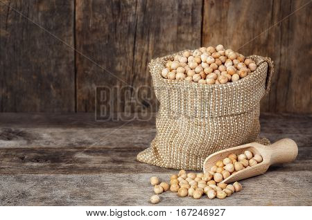 uncooked dry chickpea in sack. Chickpea in bag on table with wooden background