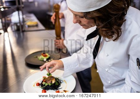 Female chef garnishing meal on counter in commercial kitchen