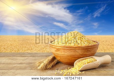 Bulgur or couscous in bowl. Bulgur in ceramic bowl and ears of wheat on table with field on the background. Ripe wheat field, blue sky with beautiful clouds and sun