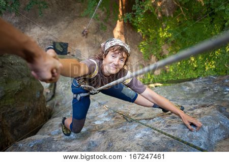 A male rockclimber is helping to old smiling female climber to reach a peak of mountain. Man giving a helping hand to the woman. View from the top poster
