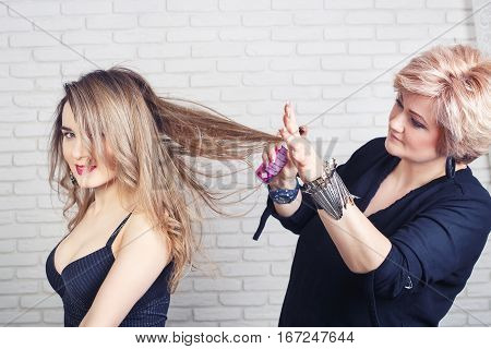 beauty, hairstyle and people concept. Young woman with middle aged hairdresser with hair spray fixating hairdo at salon. Hairdresser using hairspray on client's hair at salon