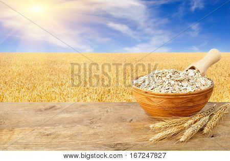 Oat flakes in bowl. Ears of oats and oatmeal in bowl on wooden table with field on the background. Ripe field, blue sky with beautiful clouds and sun. Uncooked porridge
