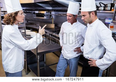 Upset head chef talking to her team in commercial kitchen