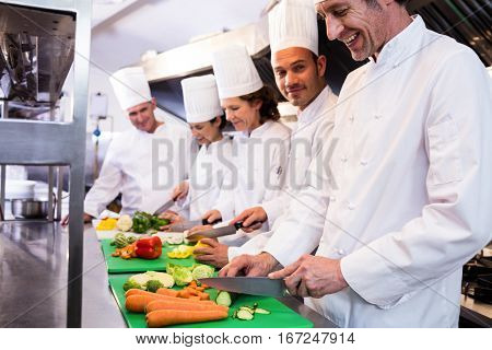 Team of chefs chopping vegetables on the chopping board in the kitchen