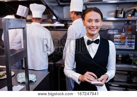Portrait of smiling waitress with notepad in commercial kitchen and chefs preparing food on background