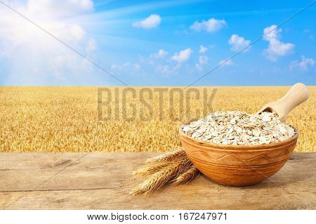 Oat flakes in bowl. Ears of oats and oatmeal in bowl on table with field on the background. Ripe wheat field, blue sky, sun. Uncooked porridge