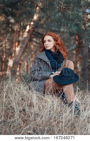 Beautiful red-haired woman. Redhead girl in autumn clothes in the forest. Redhead woman weared knitted scarf, coat, floppy hat. Portrait of dreaming woman with curly red hair outdoors