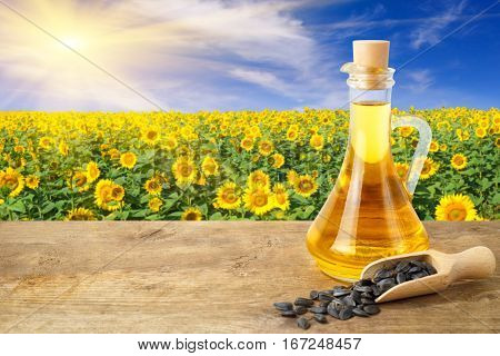 Sunflower oil in glass bottle and seeds on wooden table with sunflower field on the background. Sunflower field with blue sky and sun. Photo with copy space area for a text