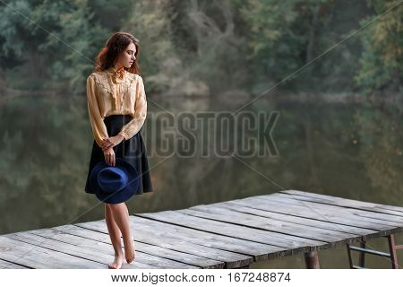 Dreaming girl on bridge with forest and river on background. Beautiful brunette woman in elegant vintage blouse with bow, skirt, floppy hat by the lake. Natural sensual caucasian woman outdoors