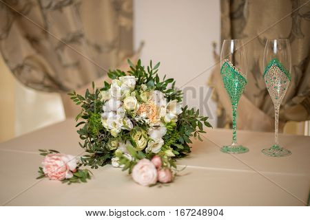 The bride's bouquet with branches of pistachio cotton branches and white roses and two champagne flutes hand-painted. Wedding concept