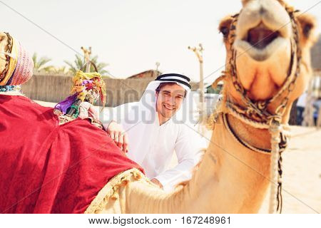 young arabian man with his camels in the desert