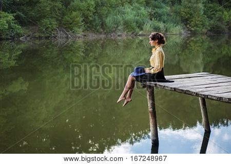 Dreaming girl sitting on bridge with forest and river on the background. Lonely sad woman by the lake. Beautiful woman in elegant vintage blouse, skirt, floppy hat. Natural sensual woman outdoors