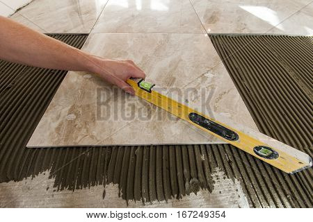 Ceramic tiles and tools for tiler. Floor tiles installation. Home improvement renovation - ceramic tile floor adhesive mortar level