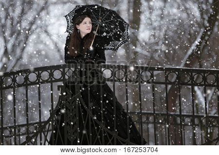 Woman in black Victorian dress in the winter park