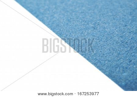 Fragment of a blue cardboard paper isolated over the white background as a copyspace shallow depth of field copyspace backdrop composition