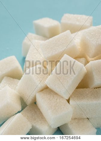 Background of sugar cubes. White cube sugar on blue background. White sugar close up
