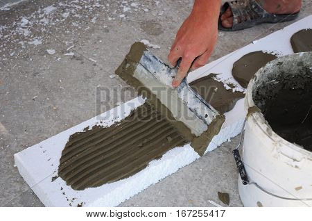 Man's Hand Plastering a Wall Styrofoam or Foam Board Insulation with Trowel. Styrofoam Insulation for Basement Walls. Installing Rigid Foam Insulation Board is Easy