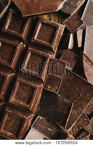 Chocolate chocolate chunks. Chocolate bar pieces. large bar of chocolate on wooden background. Chocolate candies. Background with chocolate. Slices of chocolate. Sweet food photo concept. Copyspace