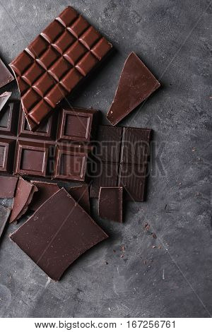 Chocolate bar pieces. A large bar of chocolate on gray abstract background. Slices of chocolate Sweet food photo concept. Copyspace