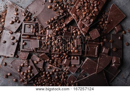 Coffee beans with chocolate dark chocolate. Broken slices of chocolate. Chocolate bar pieces. A large bar of chocolate on gray abstract background. Coffee beans. Sweet food photo concept. Copyspace