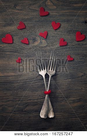 forks twined together with hearts cut outs on dark wooden background