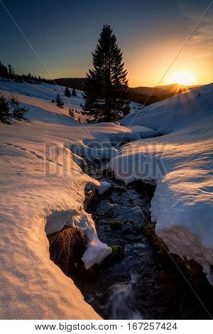 last sunrays over mountains river in snowy winter