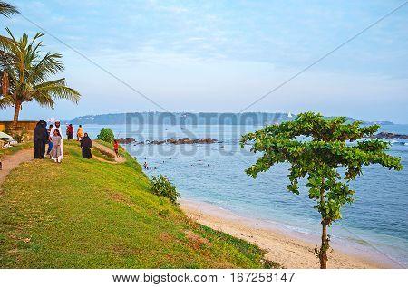 GALLE SRI LANKA - DECEMBER 3 2016: The muslim family walks along the coast of Galle Fort enjoying the sunset on December 3 in Galle.
