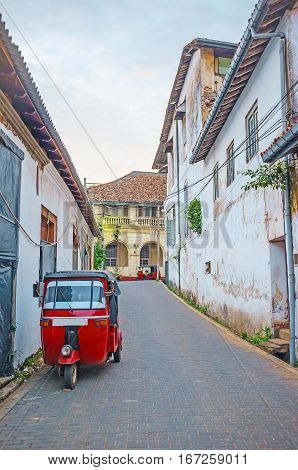 The narrow street of Galle Fort with parked red tuk tuk Sri Lanka.