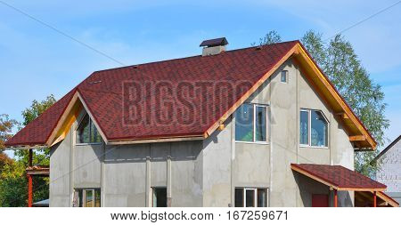 New House Roof Covered with Bitumin Tiles. Asphalt Shingles Roofing Advantages.