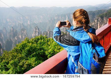 Young Female Tourist Taking Photo Of Mountains In Zhangjiajie