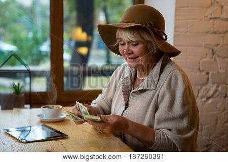 Senior woman holding money. Coffee and tablet on table. Count all savings.